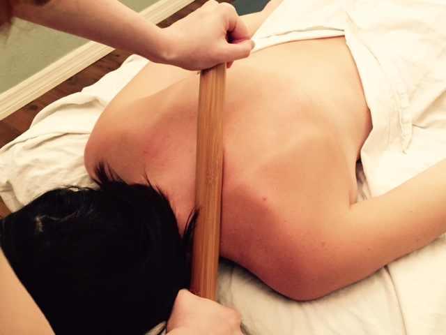 woman enjoys a warm bamboo massage